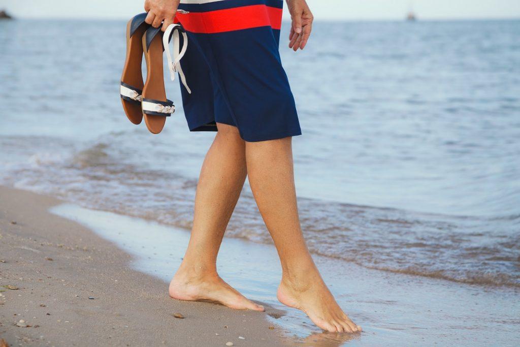 femeie-cu-sandale-pe-plaja_56432269