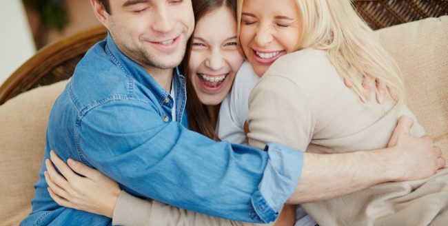 Portrait of happy family of three embracing